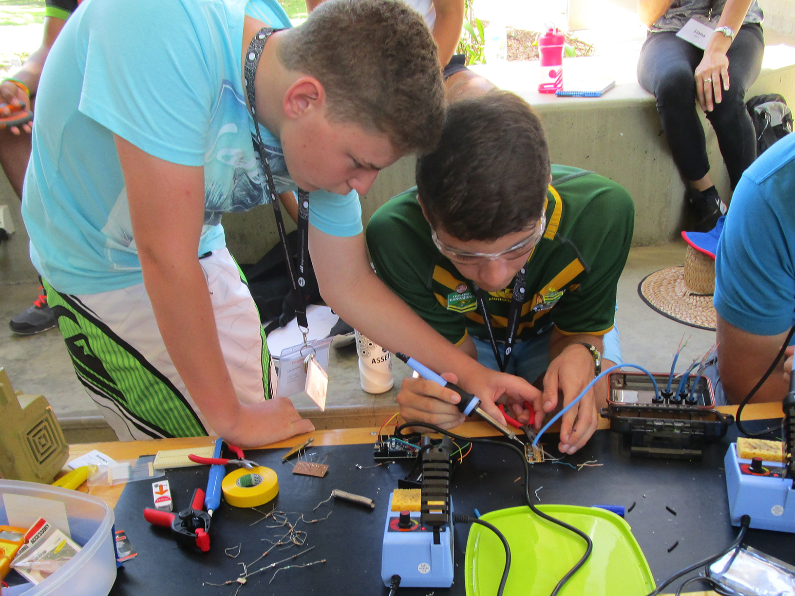 Two students soldering a sensor together