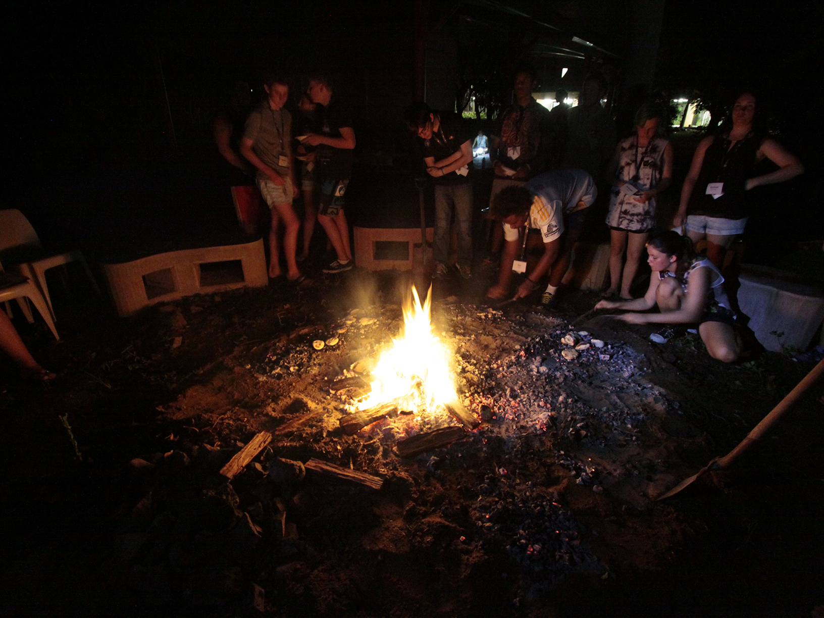 Students gather and cook on the coals of a fire