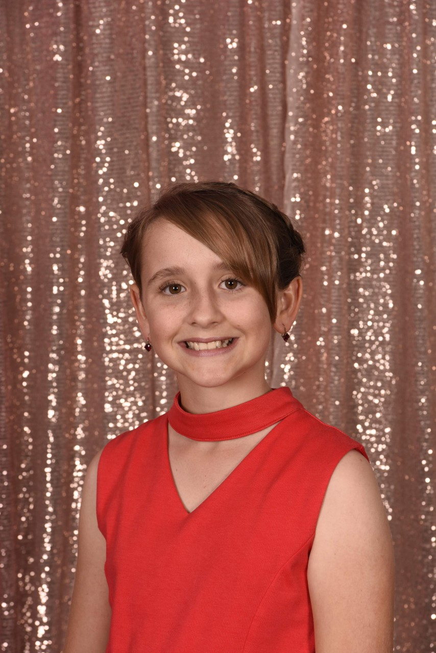 Ruby Van Tongeren in front of a gold glittery background.