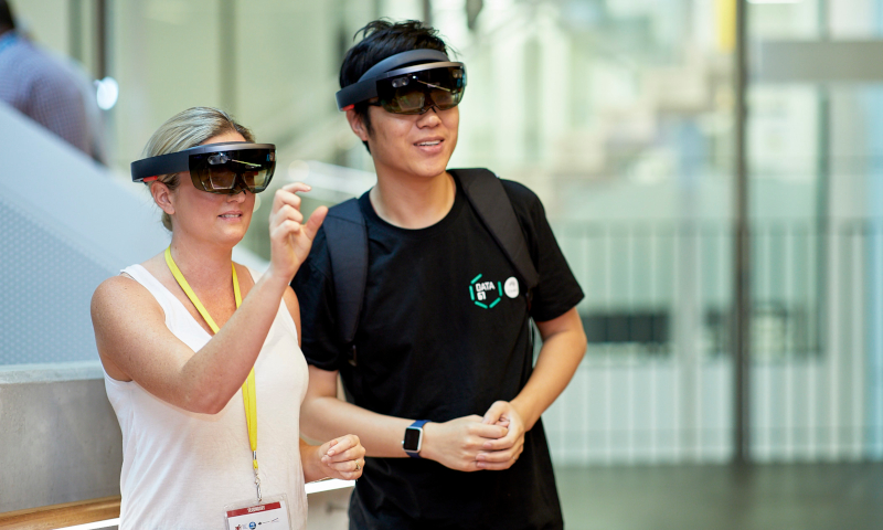 Two people standing inside a glassed area, wearing virtual reality glasses.