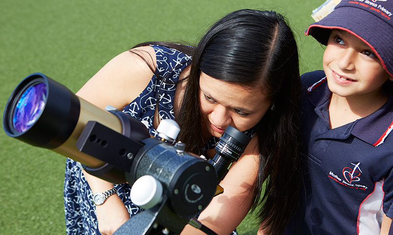 Students looking through telescope with scientist