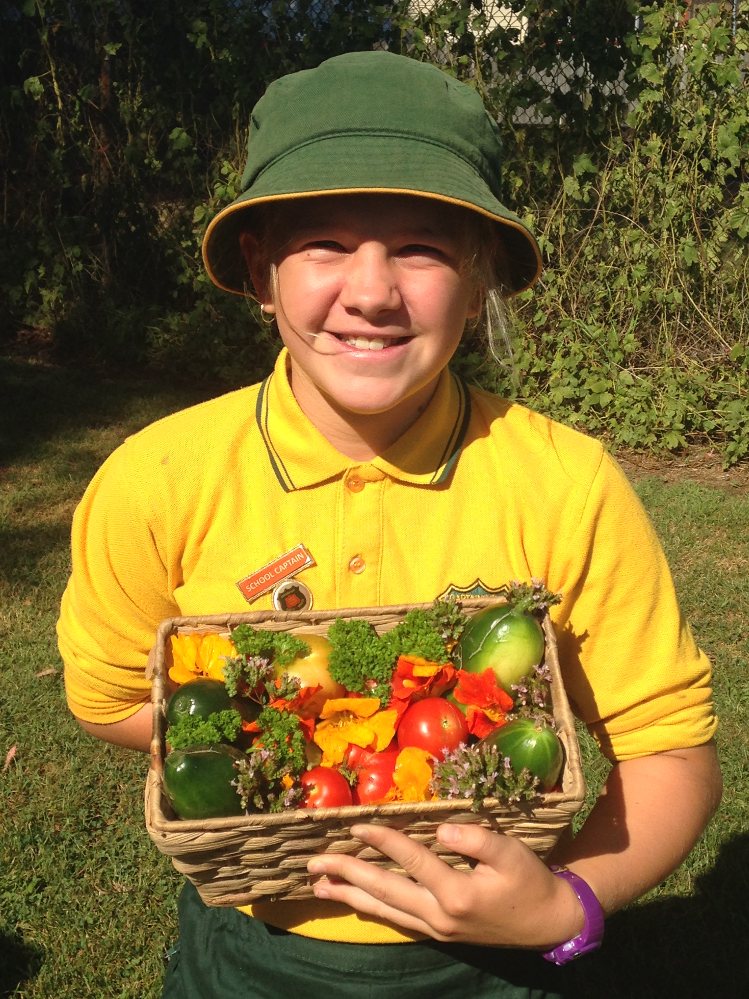 A young student showing off the produce from the school garden