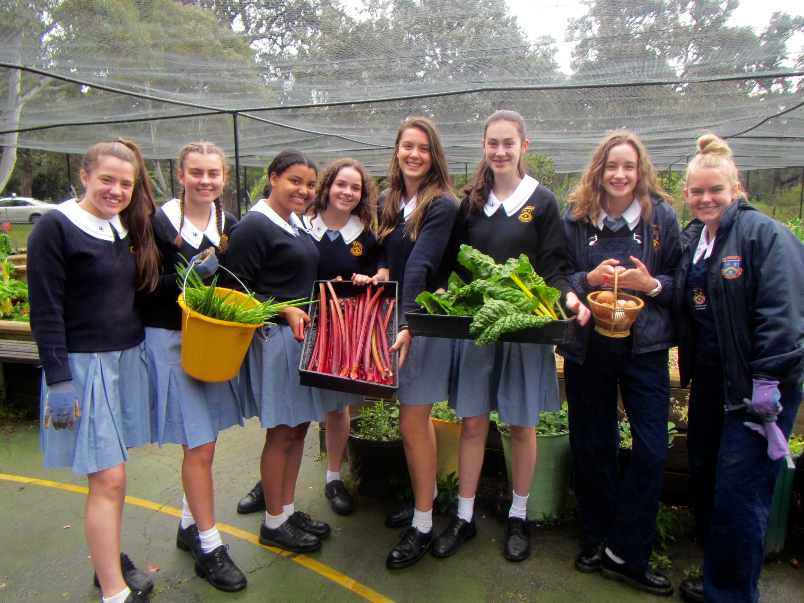 A group of students showing off the produce from their school garden