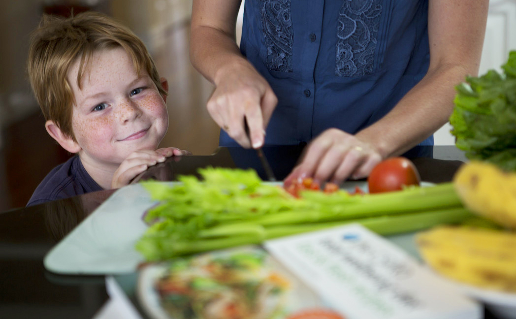 Young boy looking up at camera from corner of table while female cuts up tomatoes on chopping board