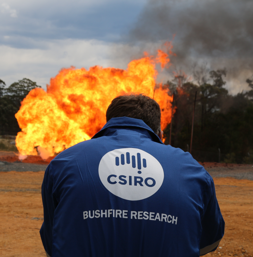 CSIRO scientist wearing a branded jacket, standing in front of flames and bushland.