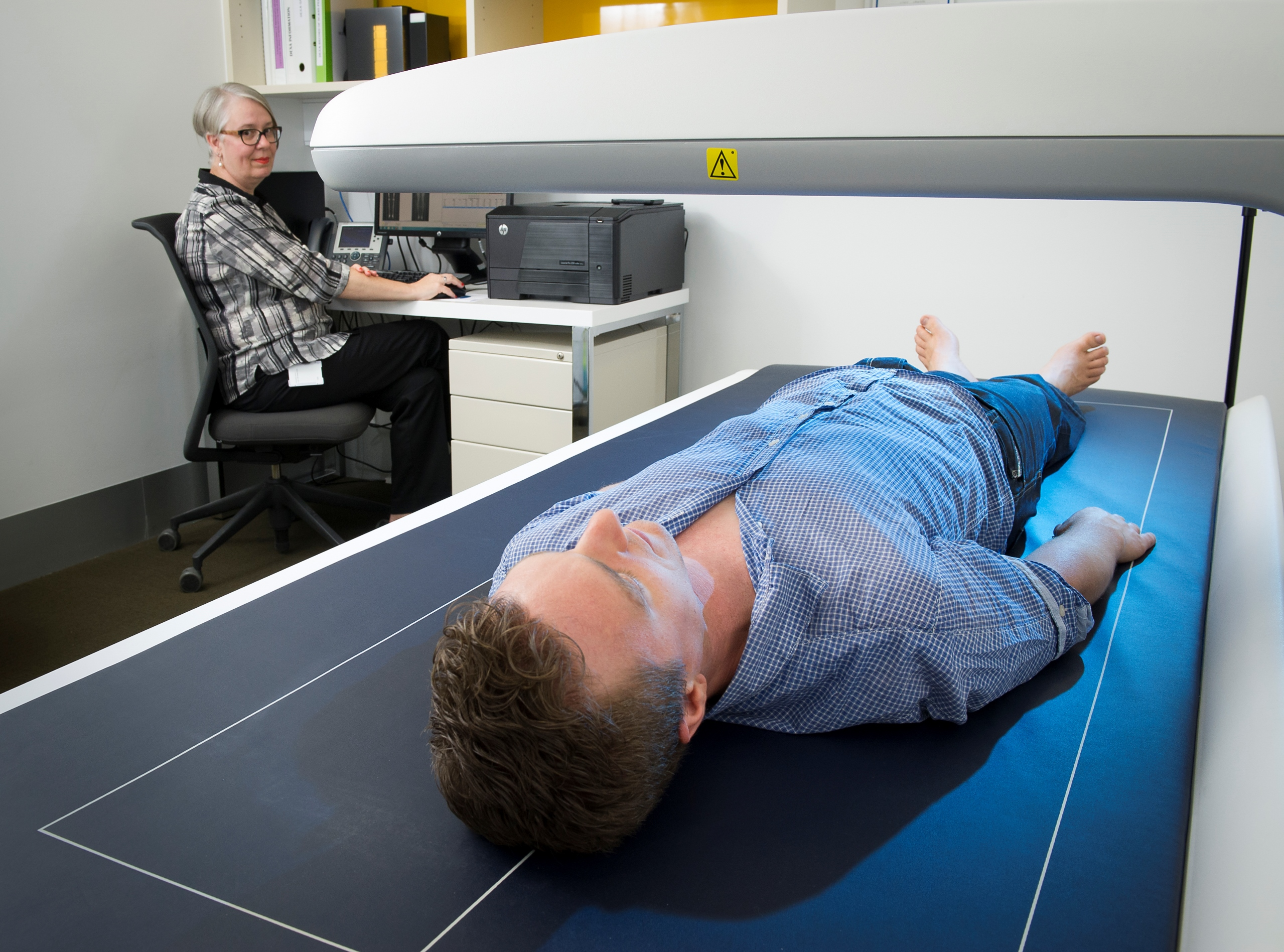 A man lying on the DEXA machine having his body composition measured.