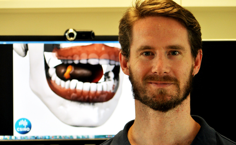 Dr Simon Harrison stands beside a monitor showing the virtual mouth model