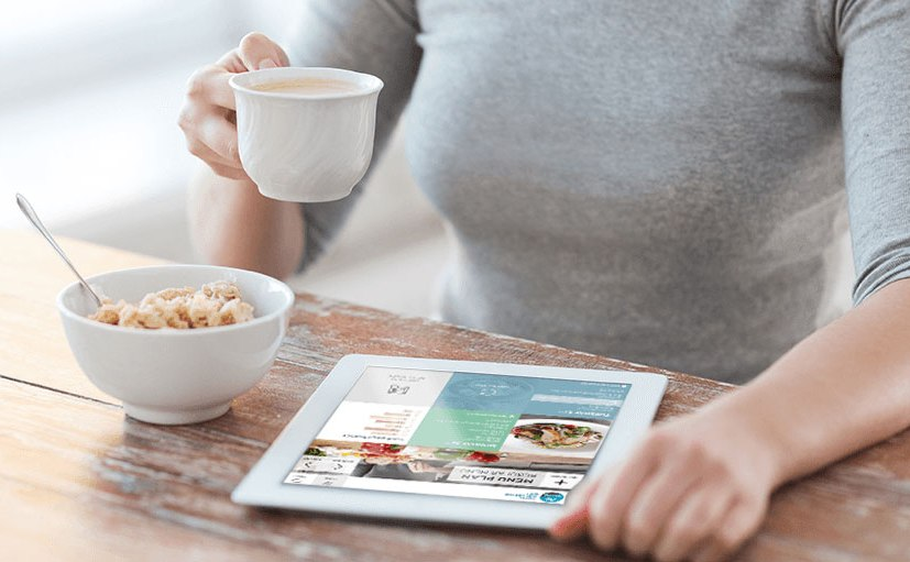A lady sitting at a table drinking a coffee and looking at diet prgram on the screen of an iPad.