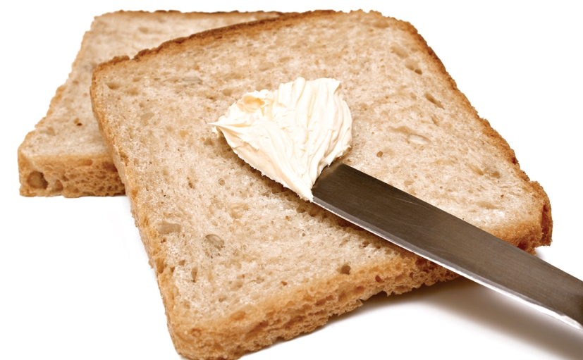 Two slices of bread and a knife with margarine.