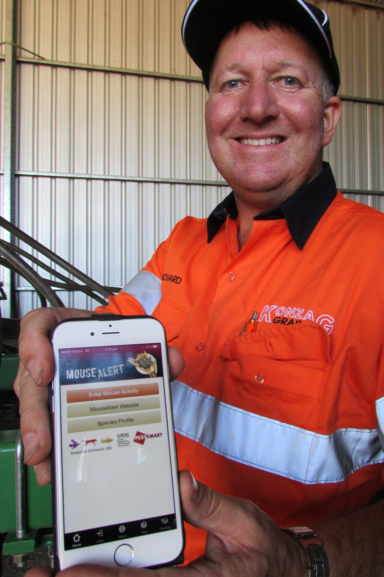 Grain grower Richard Konzag, of Mallala in South Australia, holding his mobile phone and displaying the MouseAlert app.