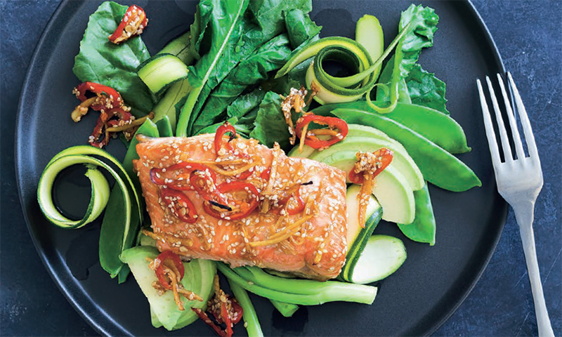 A plate of food with cooked salmon and vegetables