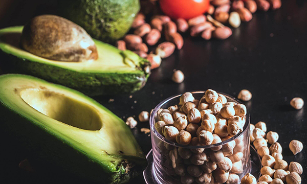 The image shows avocado and nuts, which are examples of healthy unsaturated fat sources to include in your diet