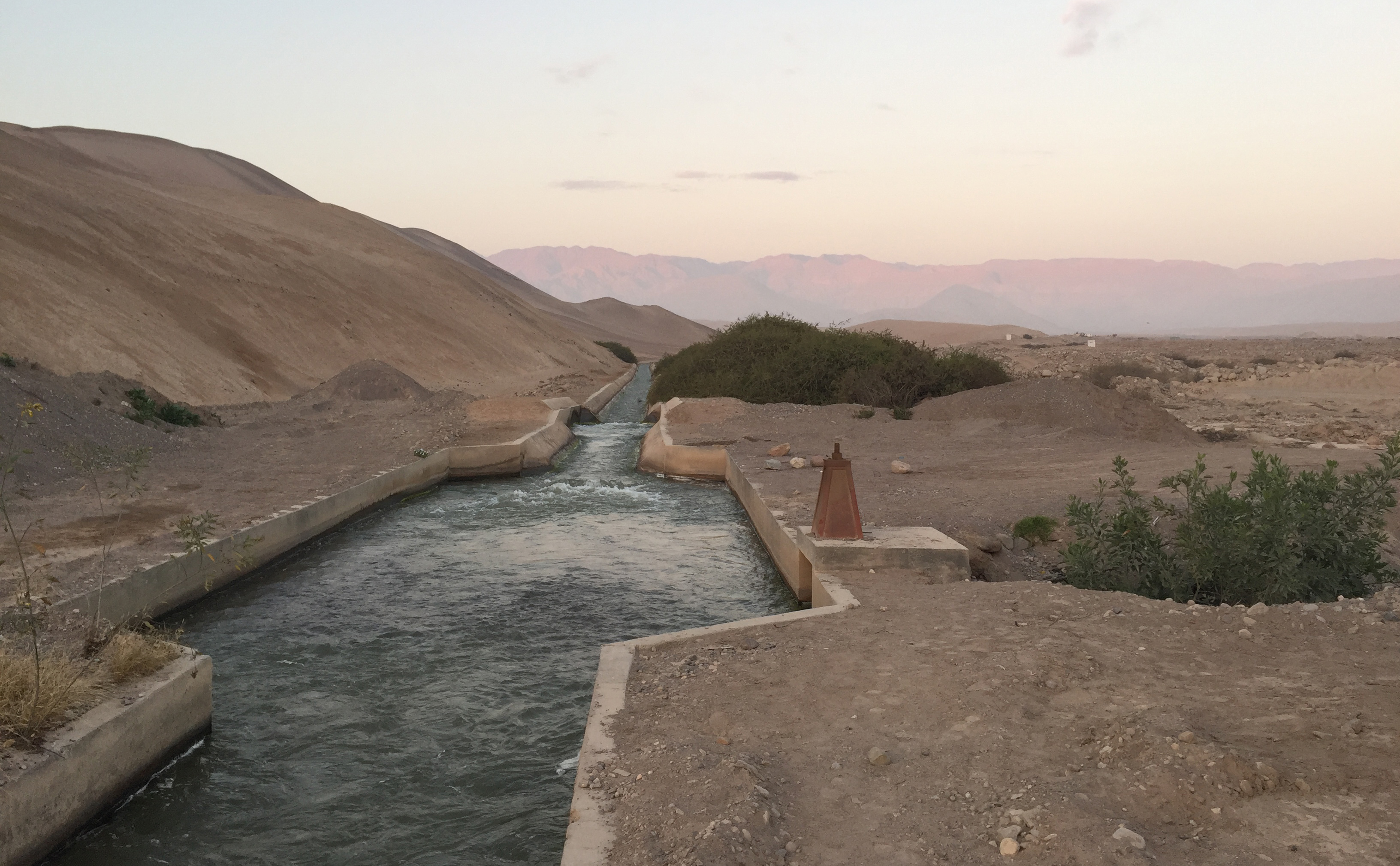 A channel full of water in a dry mountainous landscape