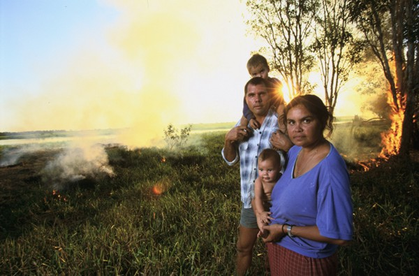 Christophersen family (mum, dad and two children) stand infront of burning wetlands in the distance