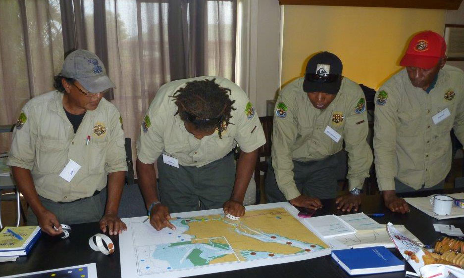 Four Indigenous rangers standing at a desk looking at a map