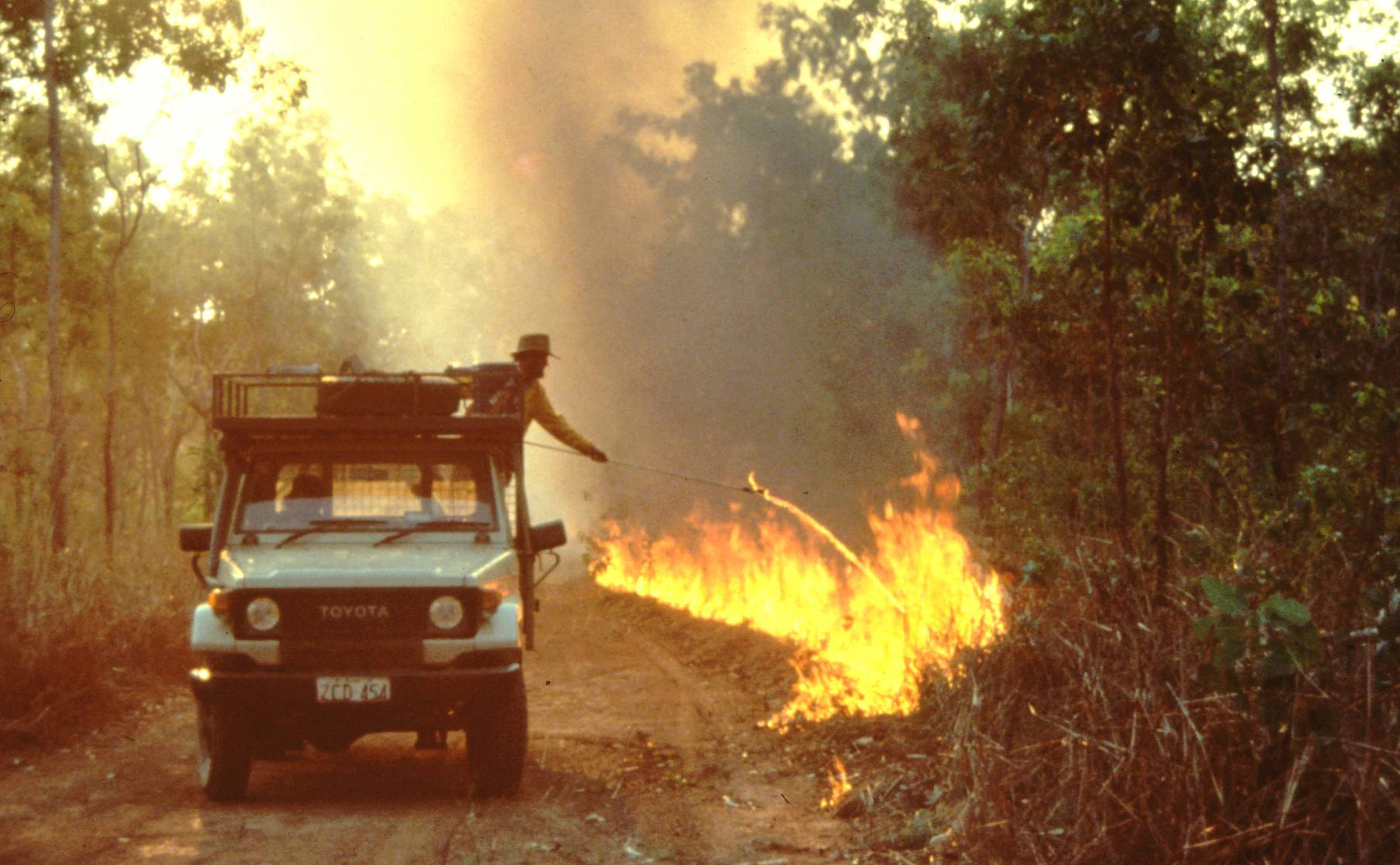 Man lighting a fire in vegetation by the roadside from the back of a four wheel drive utility vehicle