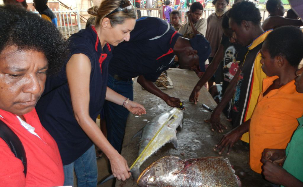 A woman inspects a fish in a crowded marketplace.