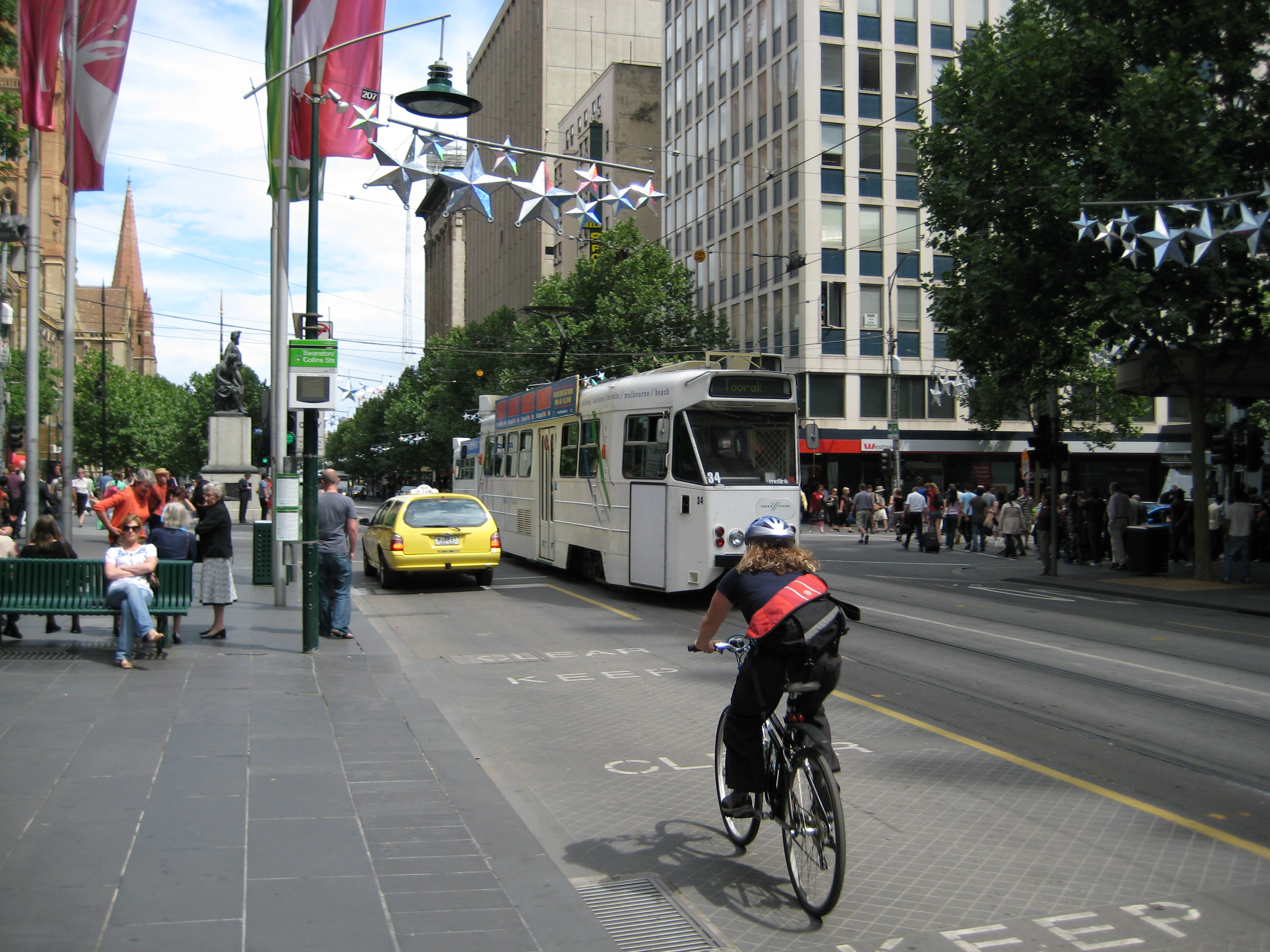 A bicycle courier on a busy Melbourne street, cycling behind a taxi. A tram is travelling in the opposite direction.