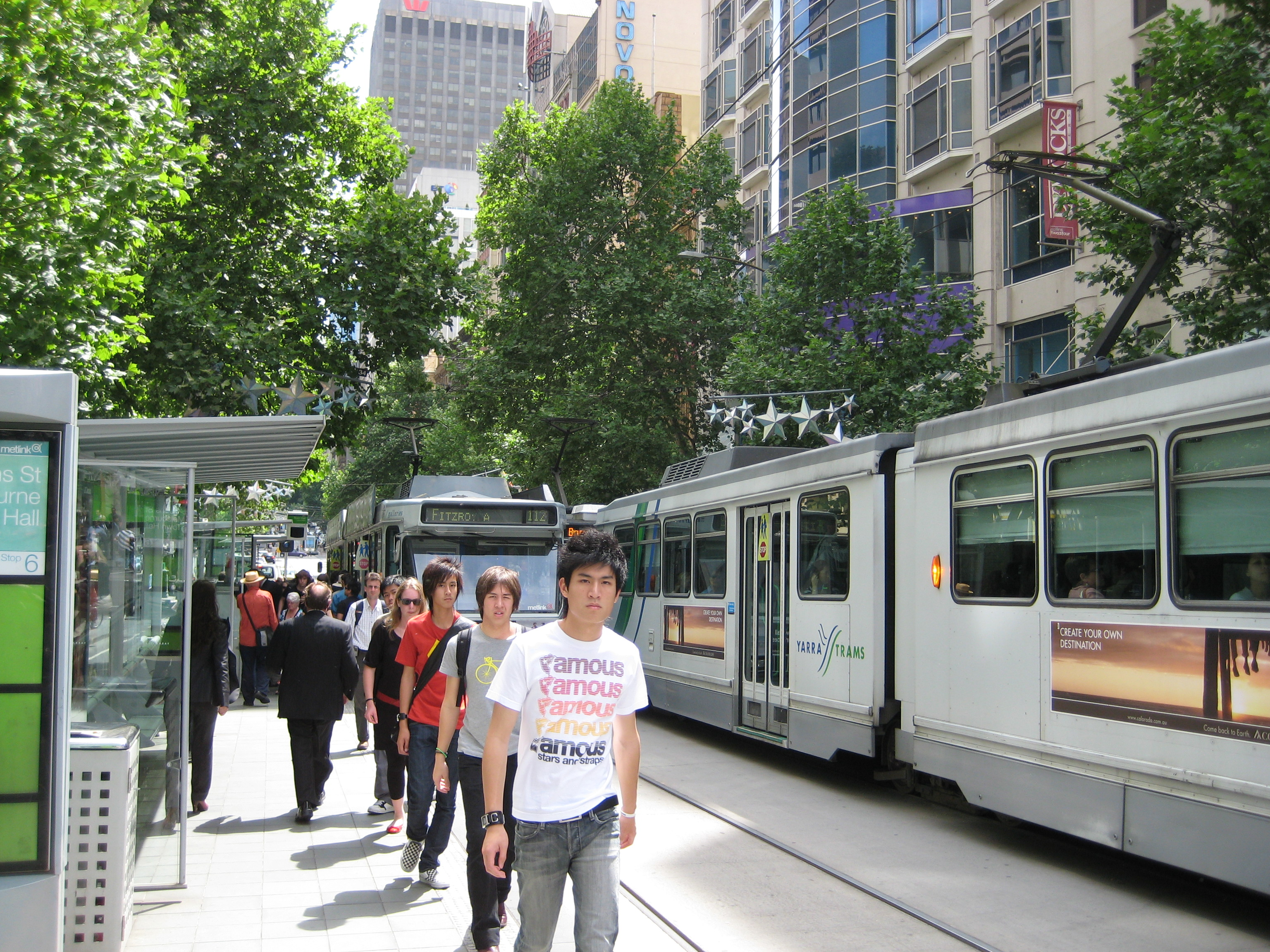 Pedestrians walking past two trams at a tram stop
