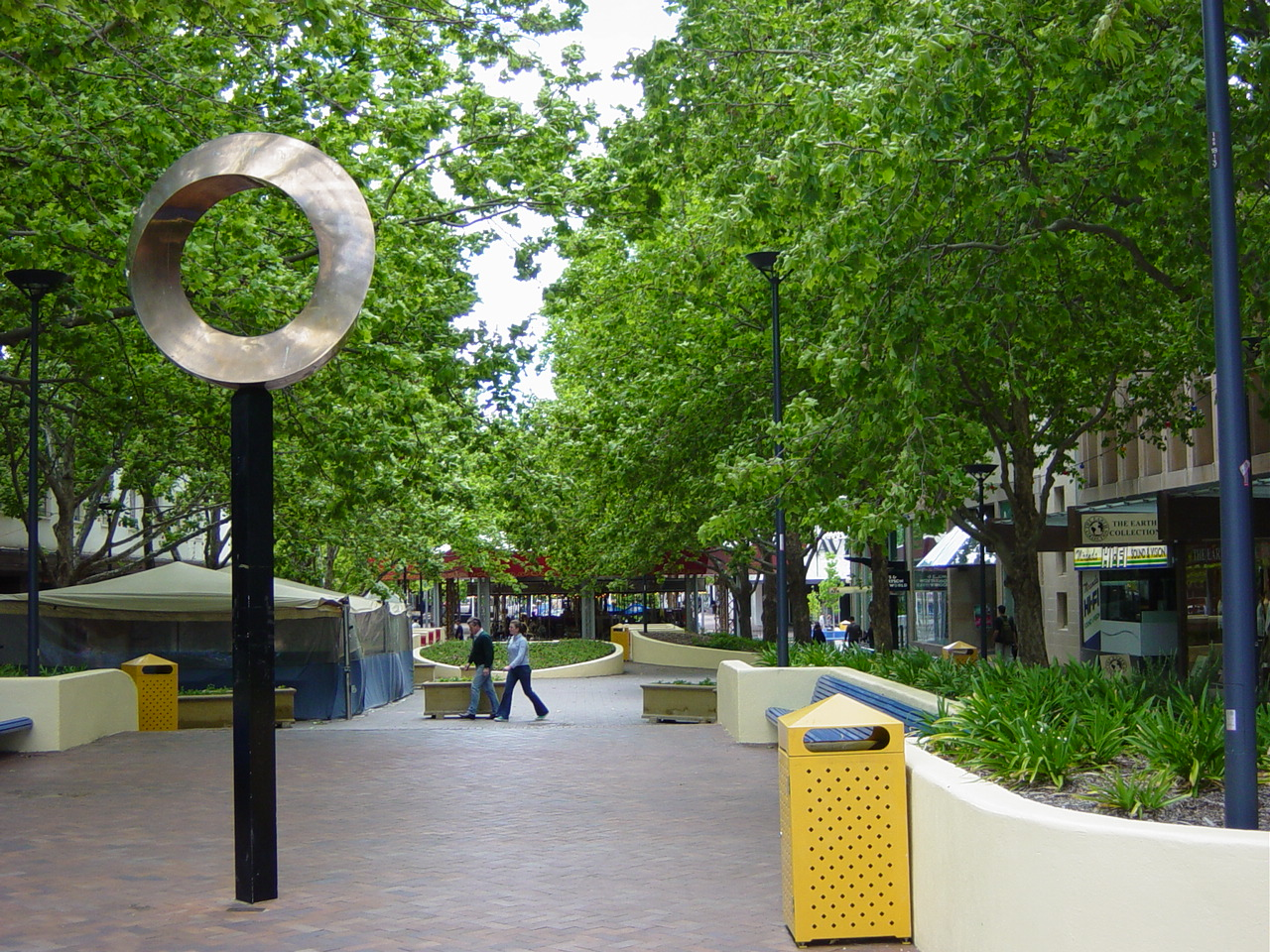 An urban pedestrian mall planted with trees and other vegetation