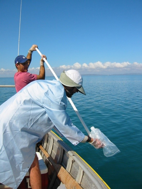 Two people leaning over the side of a boat taking water samples.
