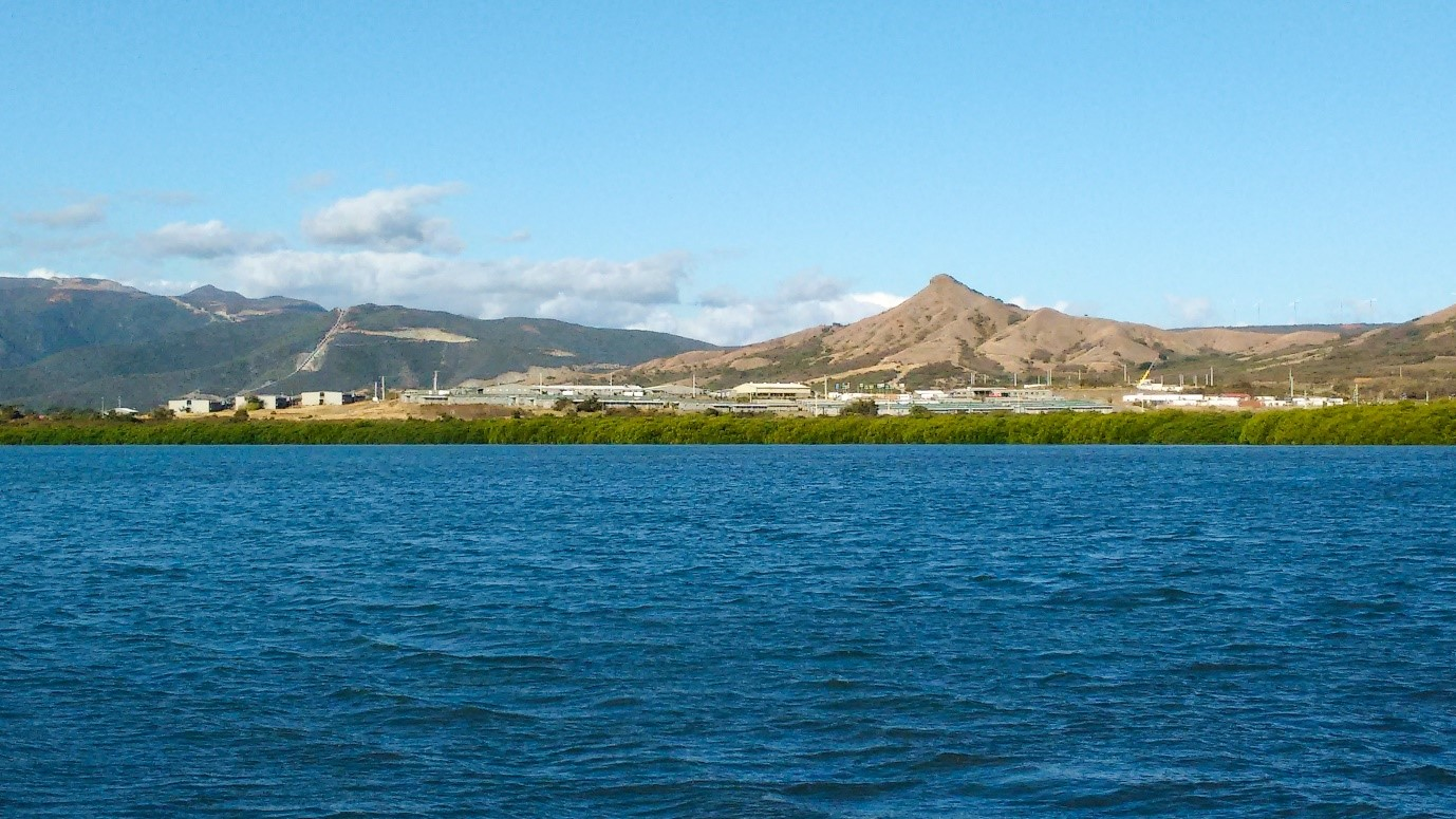 Stretch of blue water in front of mountainous landscape in the background, with buildings along the shoreline.