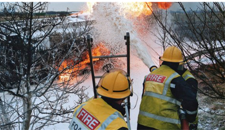 two firefighters using foam to fight fire