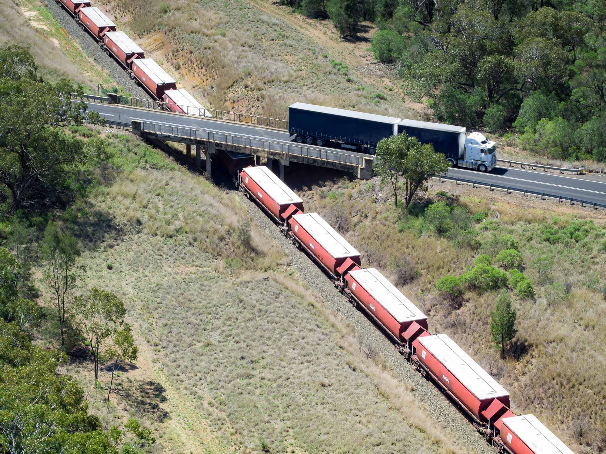 Picture of semi trailer travelling along a bridge with an image of freight train shown travelling on rail directly underneath the bridge.