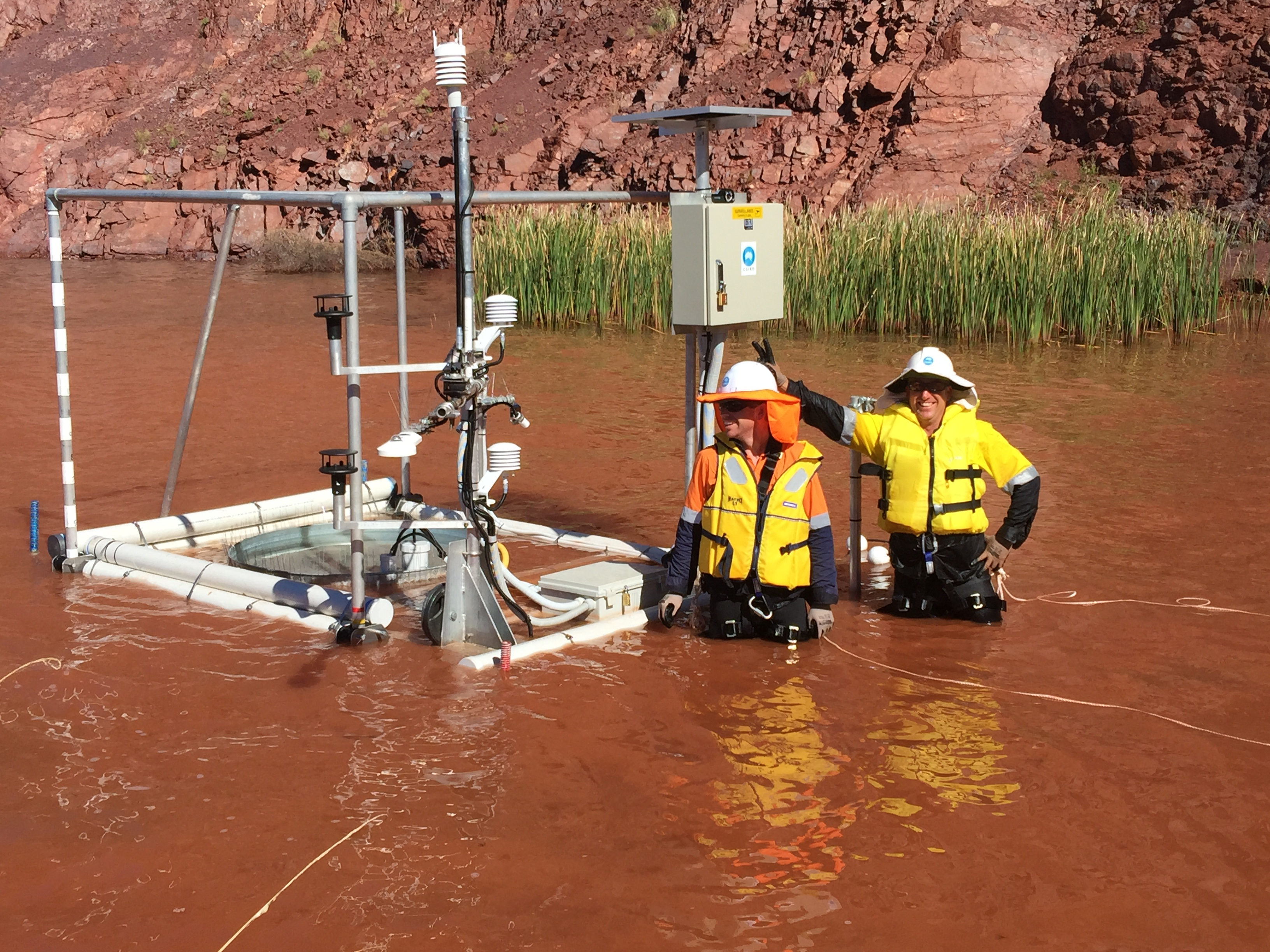 David McJannet and Aaron Hawdon standing with an Evaporation monitoring station in waist-high water.