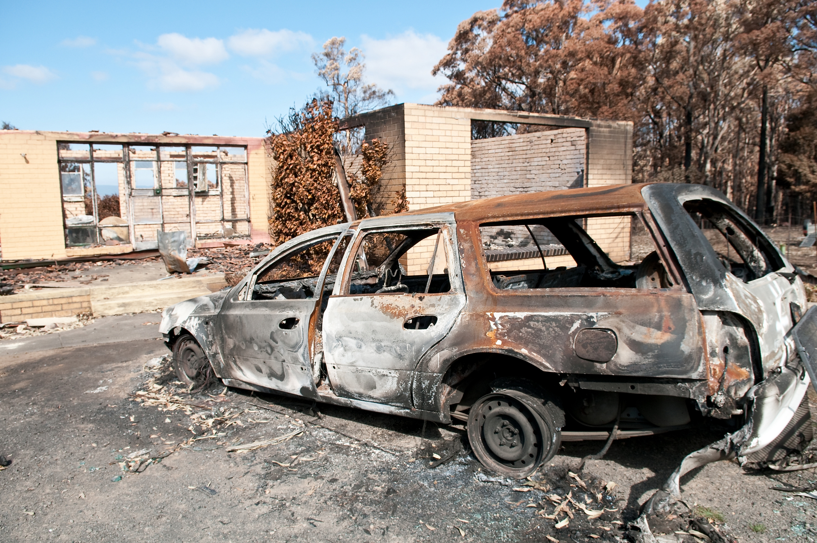 A burnt-out station wagon in front of a burnt-out dwelling, with only some walls still standing