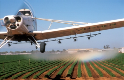 Plane flies over crops spraying them with a control agent