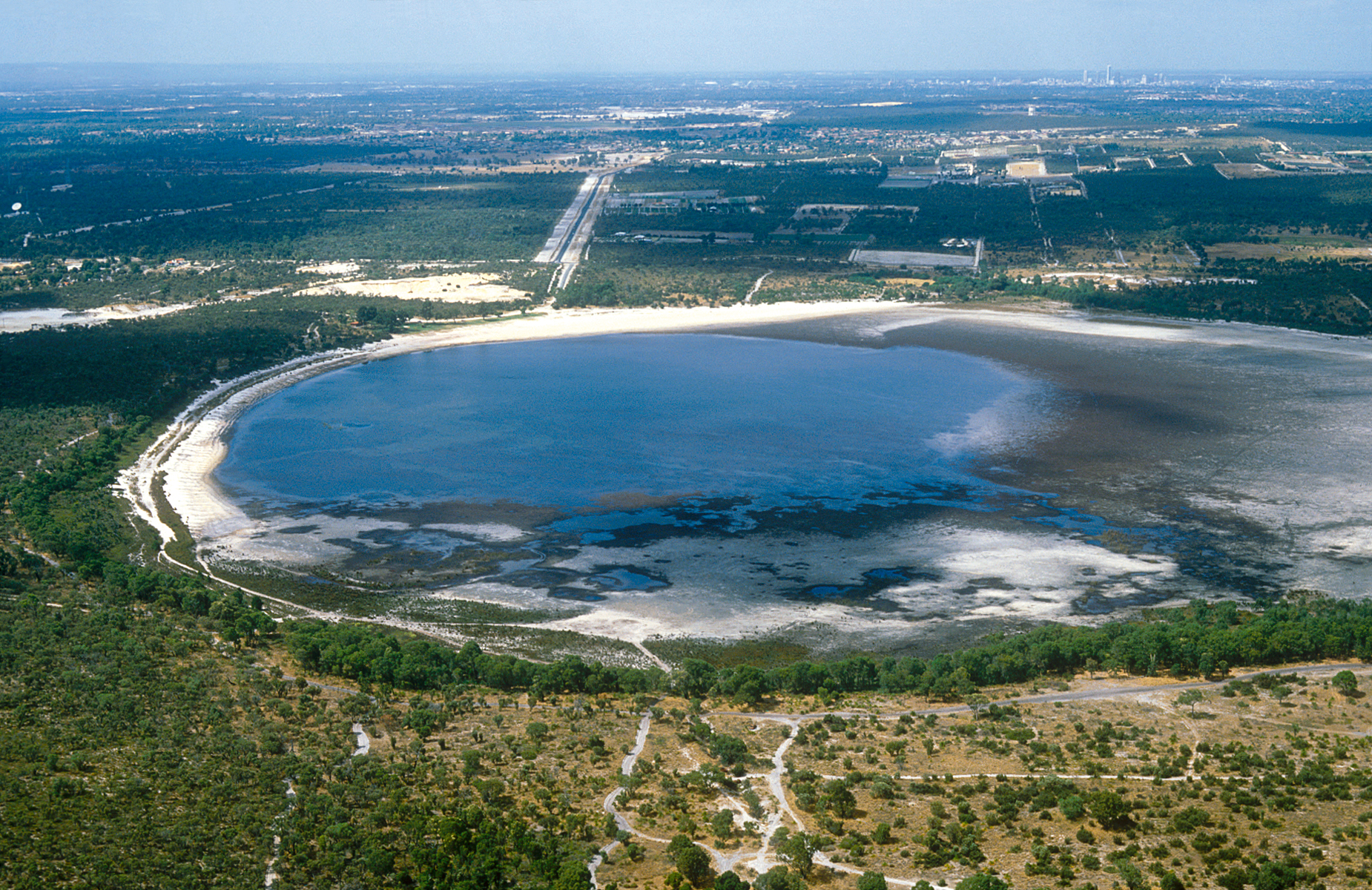 Small groundwater lake in foreground with Perth suburbs in background