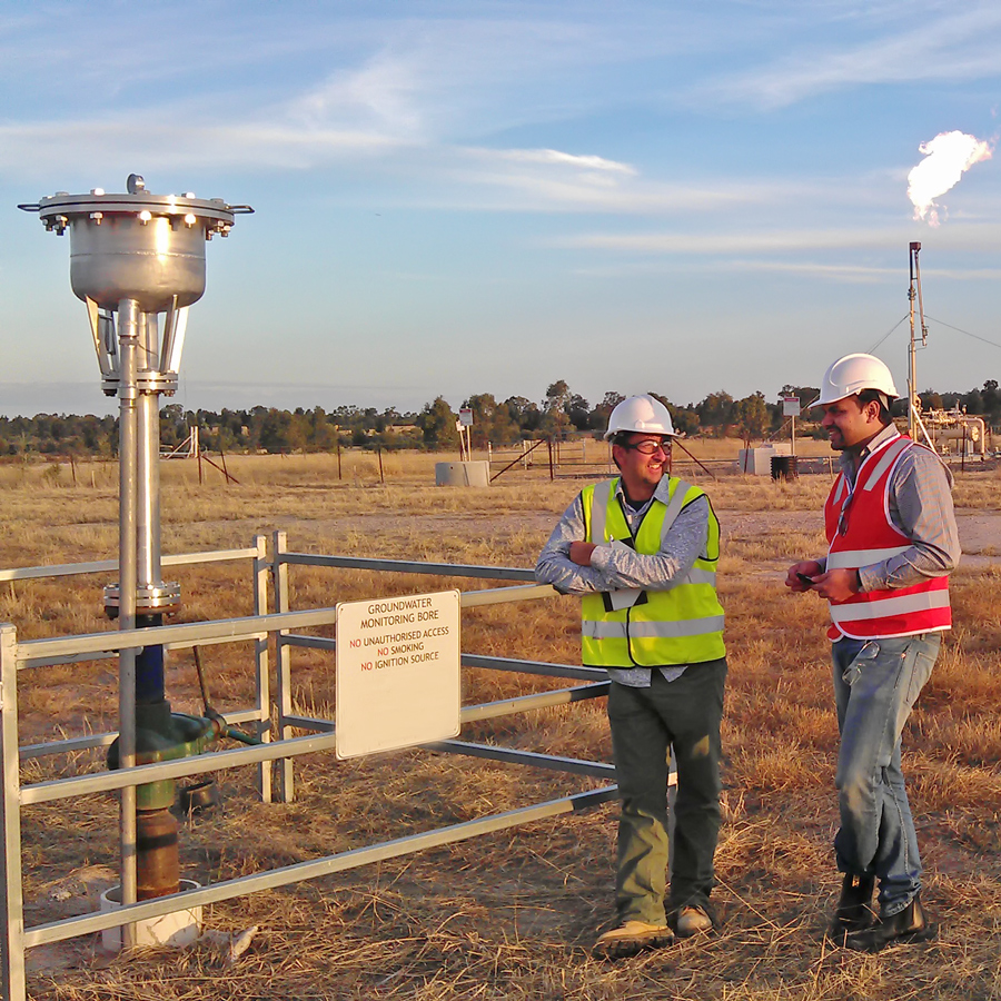 Researchers stand at a groundwater bore assessing its sustainability.