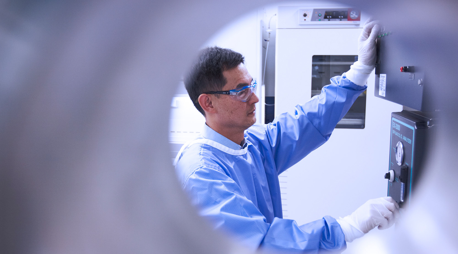 Photo of a scientist in a lab gown, gloves and safety glasses turning a dial on a 150L stirring tank bioreactor which is used for mammalian cell culture to produce recombinant protein for research.