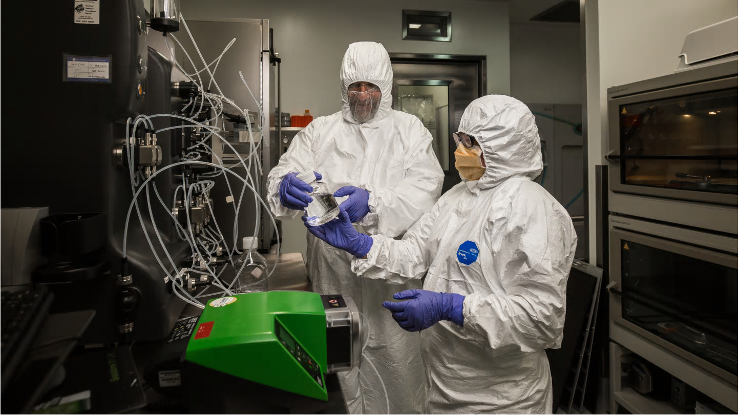 two researchers in white hazmat suits and blue gloves in a lab handling samples