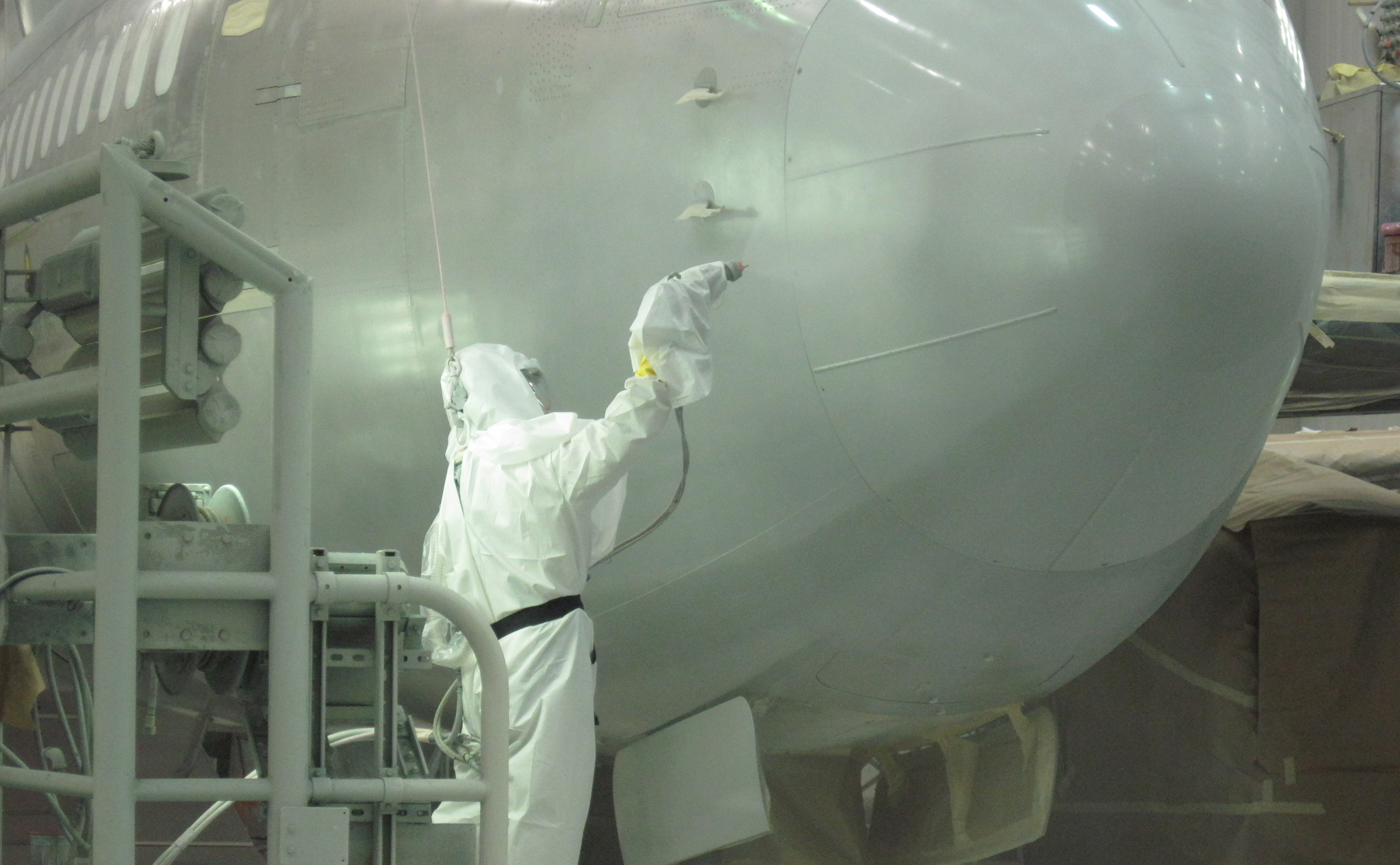 Scientist spraying topcoat technology on Boeing aircraft