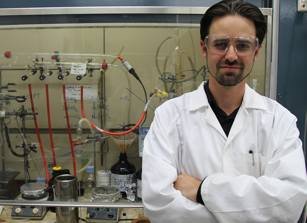 Scientist standing infront of equipment.