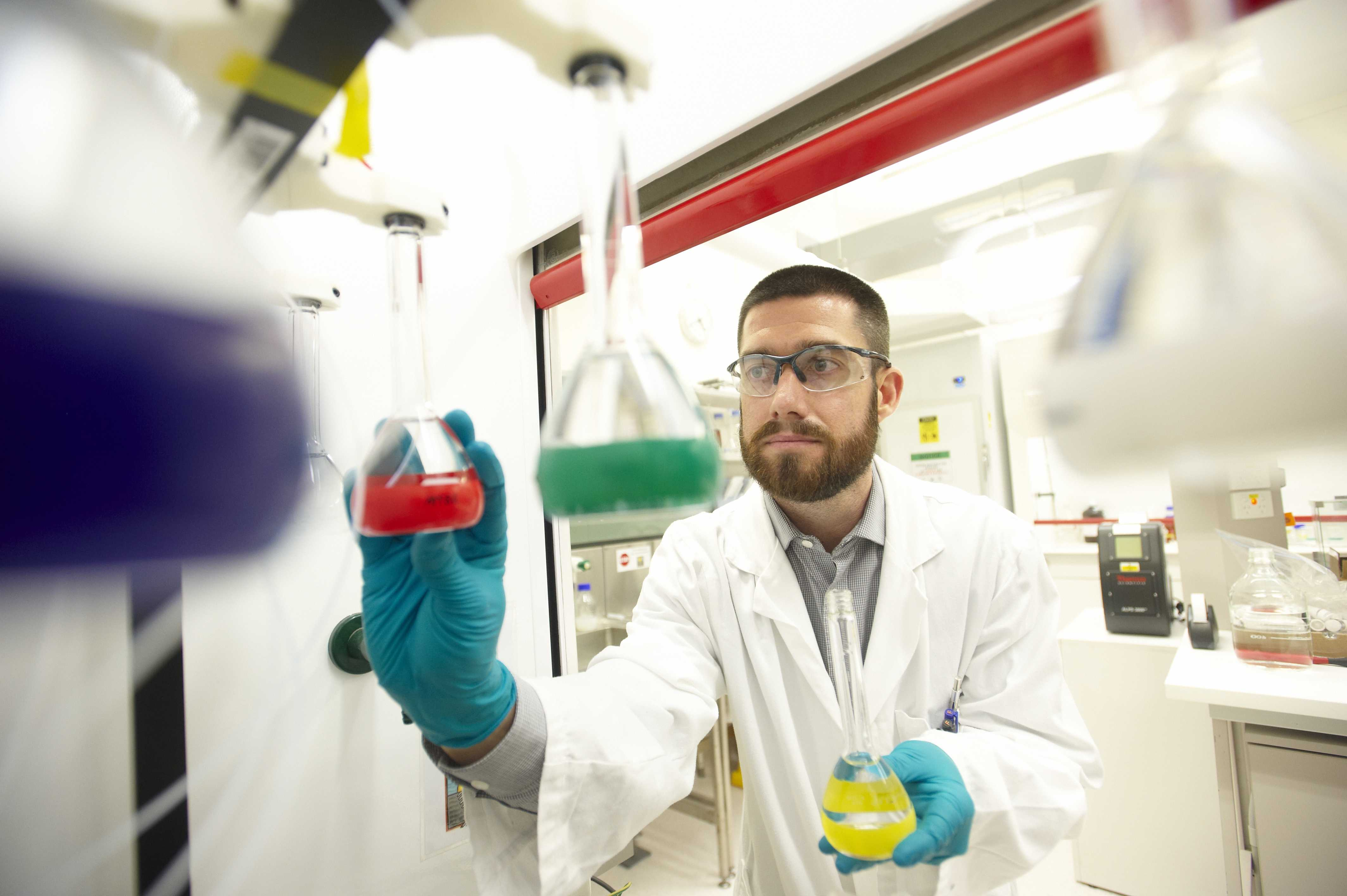 A male scientist works in the lab wearing gloves.