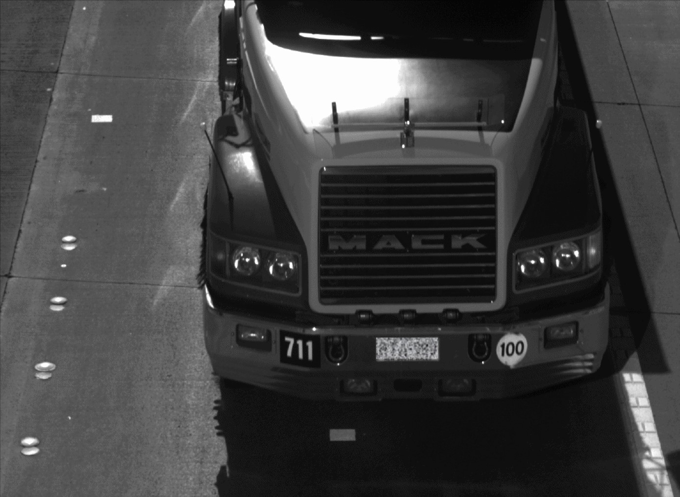 black and white close up image of front of truck, identifying number plate.
