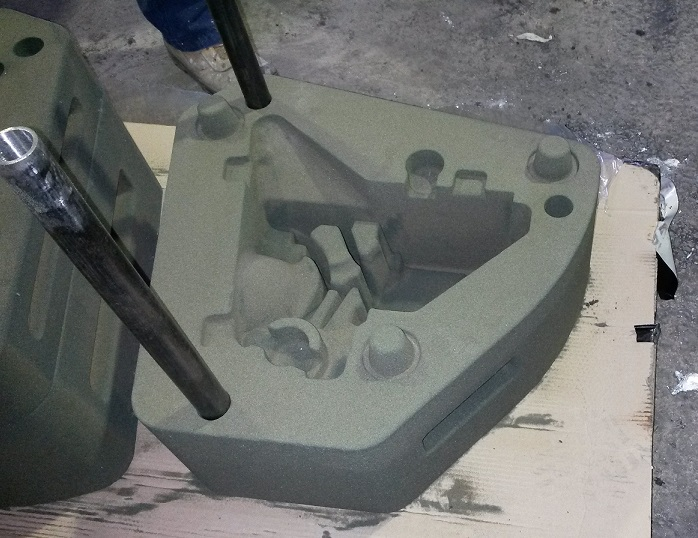 A large grey/green casting mould of a complicated shape - for a component of the Hawkei vehicle. It is sitting on a piece of cardboard on the floor of the CSIRO Lab.