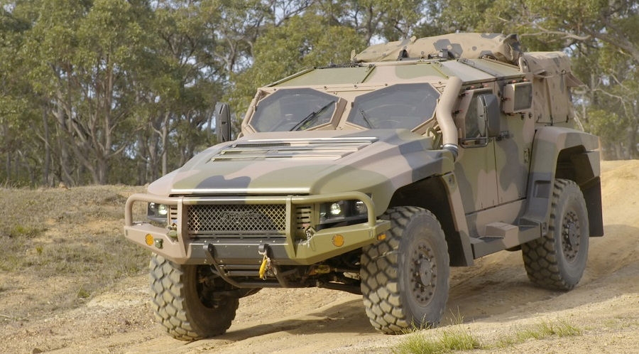 Camouflaged army vehicle (The Hawkei Protected Mobility Vehicle) driving on bush track, with bushland inbackground