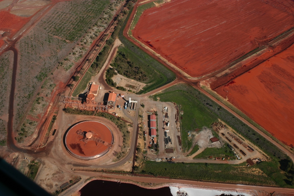 Aerial view of bauxite processing facility showing red mud ponds