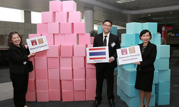 Three people standing in front of blocks signifying a country's material usage