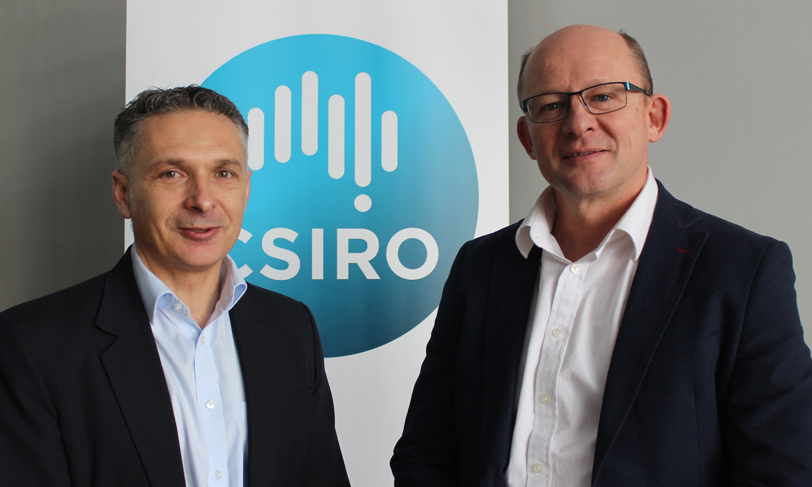 Two men standing infront of banner with CSIRO logo
