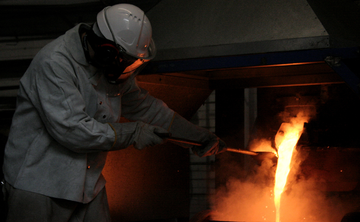 Heavily protected helmeted worker beside furnace with molten metal flowing out of chamber