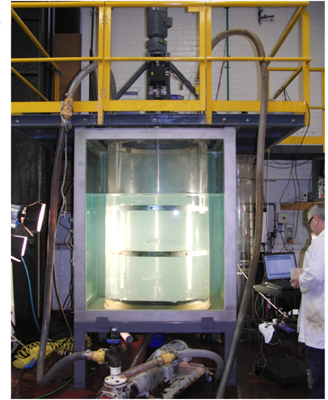 Solvent extraction equipment with chemist. Looks like a large glass cylindrical tank filled with clear fluid.