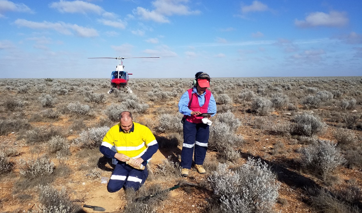 Male and female scientists taking soil sample in remote area using a helicoptor to move from place to place