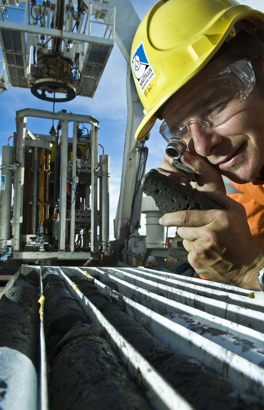 Man looking at soil core samples from the seafloor.