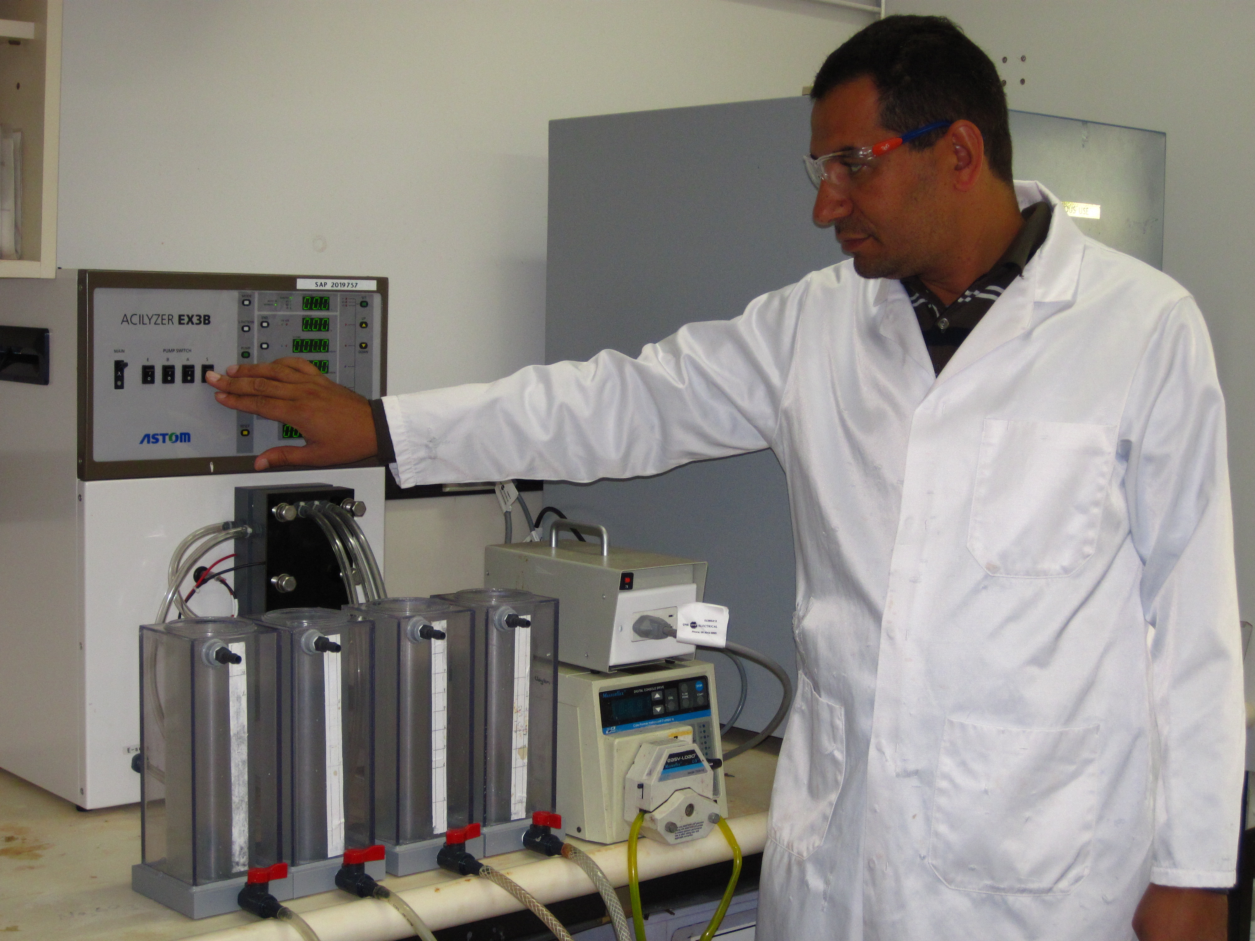 Scientist in white lab coat standing in front electrodialysis unit in CSIRO's Waterford laboratory.