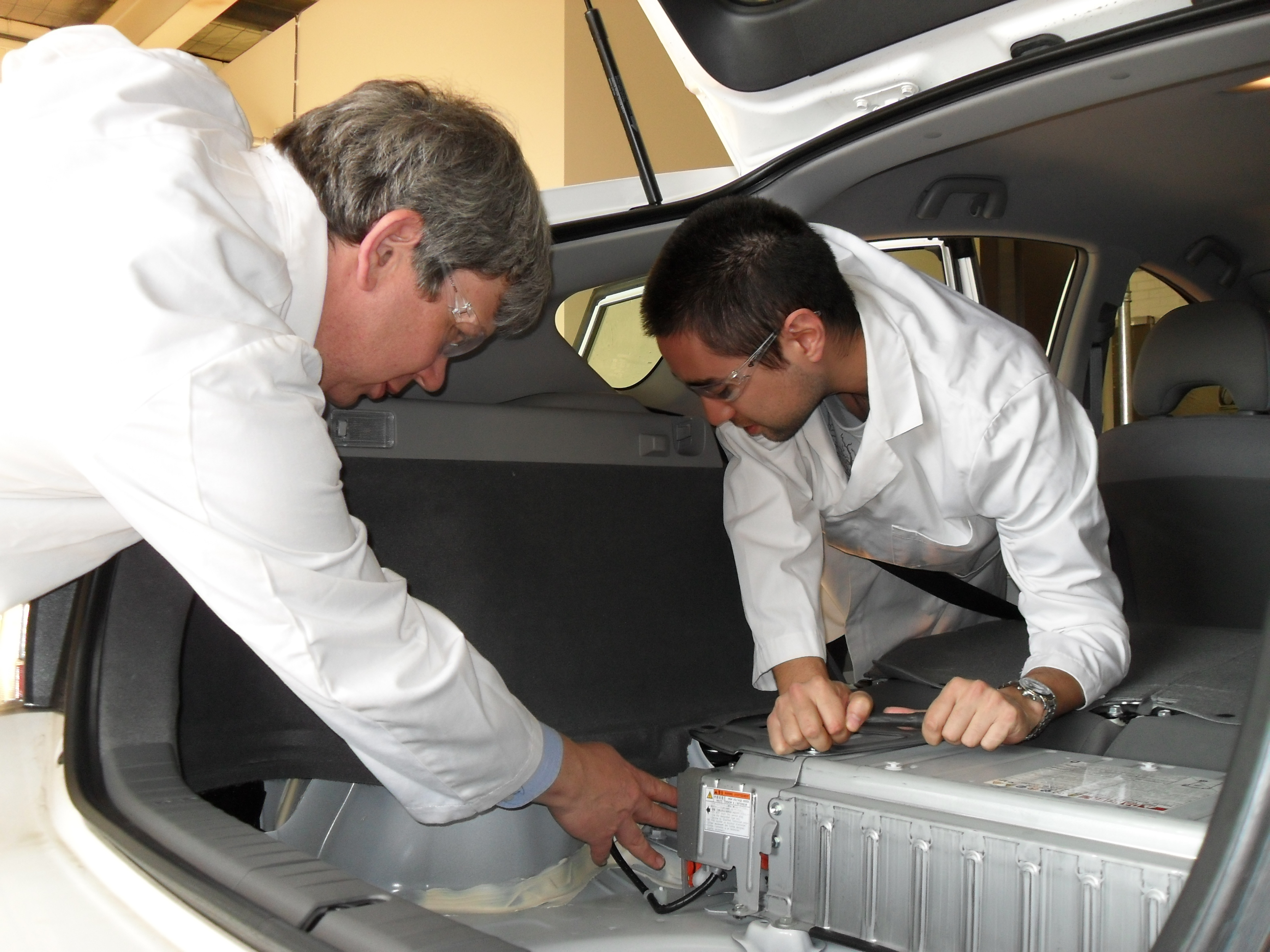 Two scientists working on battery pack in boot of modified plug-in electric vehicle